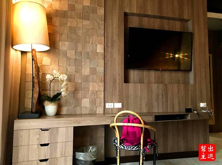 電視牆面是木紋簡單風,另外一邊就是躺椅沙發