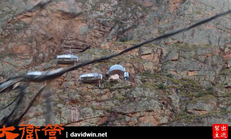 山壁上有著幾個建物,這是透明騰空的膠囊旅館